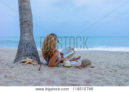 Woman on the beach under the coconut trees