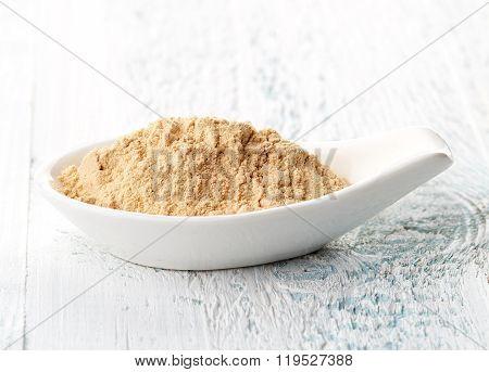 Maca Powder In White Porcelain Spoon