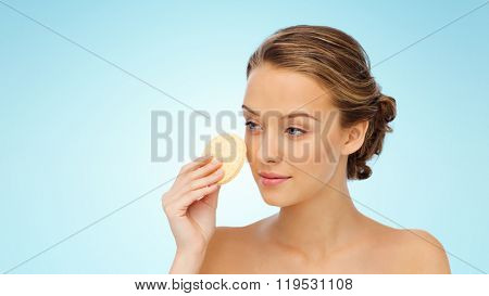 beauty, people and skincare concept - young woman cleaning face with exfoliating sponge over blue background