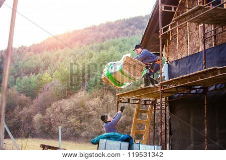Construction workers thermally insulating house facade, standing