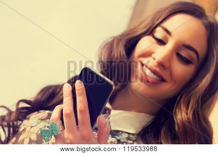 Young urban girl typing messages on her smartphone.