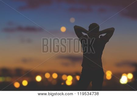 Silhouette of a man with de-focused city lights in the background.