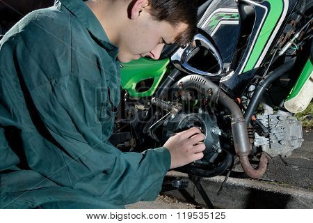 Teenage Boy Working On A Motorbike Enginge