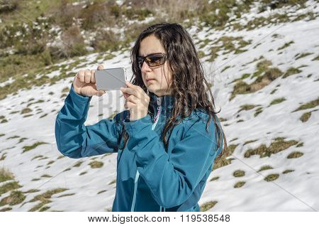 Woman Taking Photo With Her Smartphone In Winter Mountains