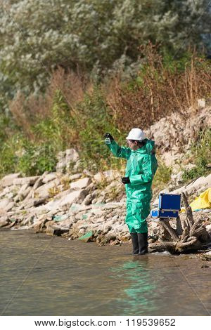Environmentalist Looking At Sample Of Polluted Water