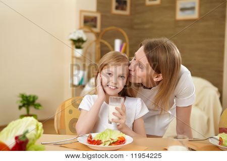 mother with teenager daughter having meal at home