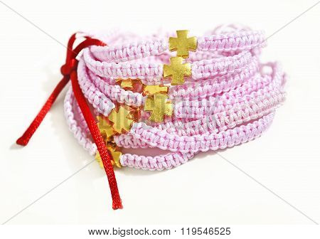 pink macrame bracelets with gold cross and red ribbon poster