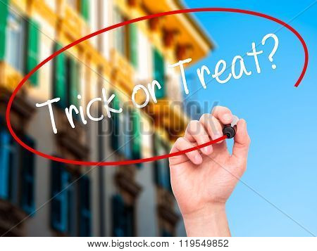 Man Hand Writing Trick Or Treat? With Black Marker On Visual Screen.