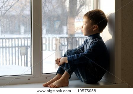 Boy Sitting On The Window Looking Out