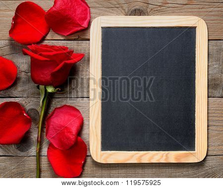 Red Rose And Blackboard On Wooden Table For Menu Template
