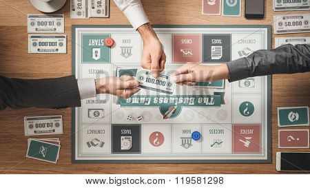 People playing a business board game on a wooden table challenging each other and holding a banknote poster