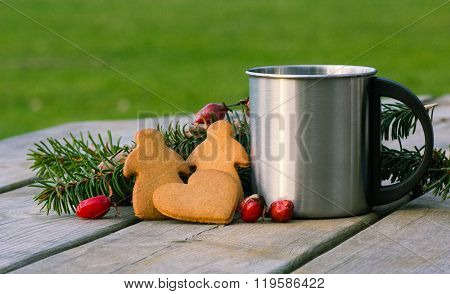 Cinnamon and ginger cookies man and woman and heart on a table with pine branch and red winter berri