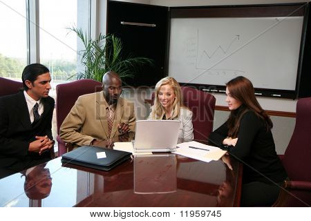 Business Team sitting around a computer in an office