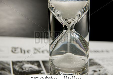 Completely Filled Sandglass On Newspaper
