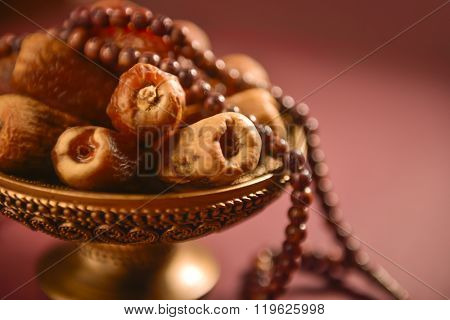 Religious food and objects. Close up of arabic dates and rosary.