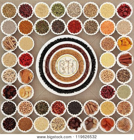 Large dried super food sampler in porcelain bowls forming an abstract background  over hessian. Highly nutritious in antioxidants, minerals, vitams and dietary fibre.