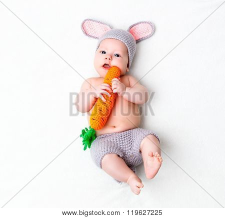 Happy Baby Child In Costume A Rabbit Bunny With Carrot On A White
