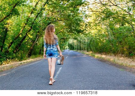 Beautiful Girl In Blue Plaid Shirt Walking On An Empty Road Between Green Trees