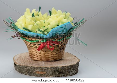 simple handmade artifact - basket with flowers made of colored foam rubber yellow. Imitation of spri