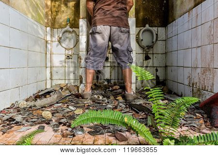 Man peeing in ruined and abandoned  tropical toilets