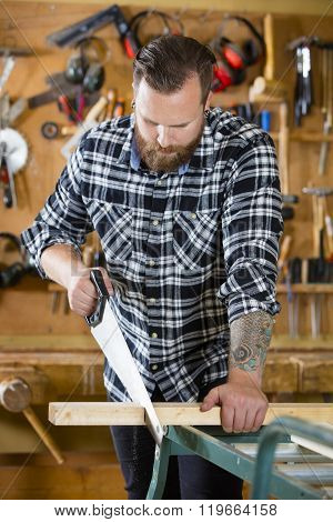 Carpenter sawing wood with hand saw in workshop