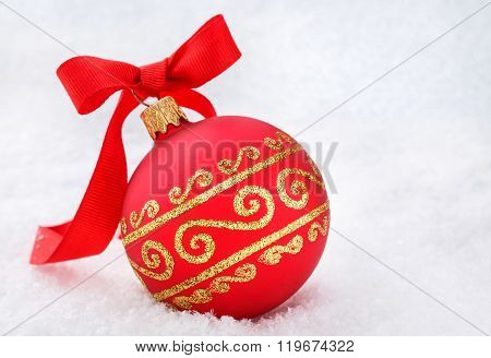 Red Christmas ball with ribbon in the snow