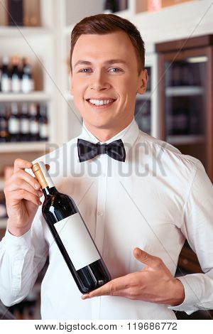 Professional sommelier holding wine bottle