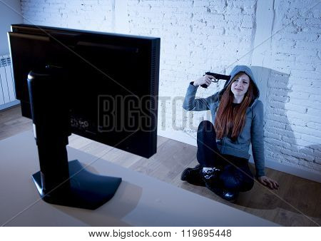 young teenager woman abused suffering internet cyberbullying scared and desperate pointing gun to her tempo in suicide gesture in front of computer monitor in cyber bullying concept