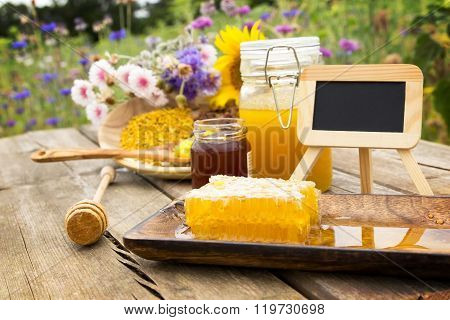 A chalkboard surrounded by many apiculture products on a wooden table ** Note: Shallow depth of field