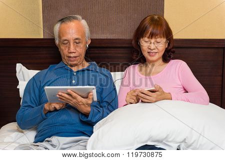 Asian Senior Couple With Mobile Technology