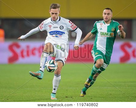 VIENNA, AUSTRIA - OCTOBER 29, 2014: Lukas Spendlhofer (#23 Sturm) and Steffen Hofmann (#11 Rapid) fight for the ball in an Austrian soccer league game.