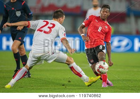 VIENNA, AUSTRIA - OCTOBER 12, 2014: Marko Simic (#23 Montenegro) and David Alaba (#8 Austria) fight for the ball in an European Championship qualifying game.
