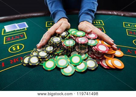Poker player going all-in pushing his chips forward