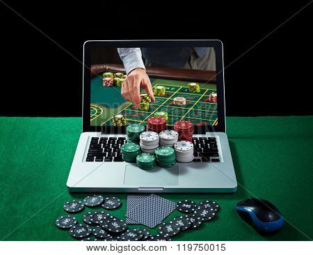 Green table with casino chips and cards on notebook