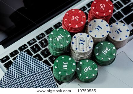 View of casino chips, cards on laptop to play online.