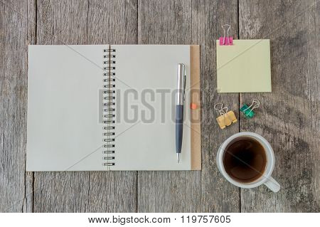 Open Notebook On Wooden Background With Coffee Cup And Yellow Note Paper.