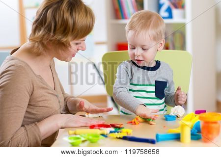 Kid Boy And Mother Play Colorful Clay Toy In Nursery