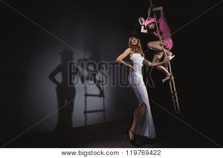Circus actress with funny pink rabbit sitting on rope ladder