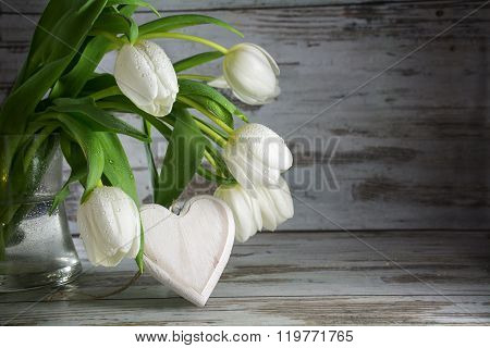 White Tulips And A  Heart Shape Of Wood Against A Vintage Wooden Background, Love Concept