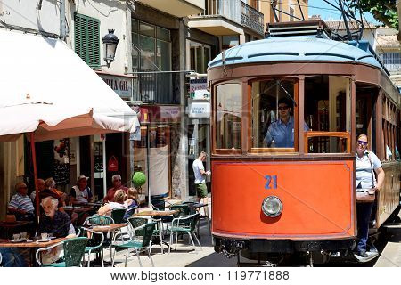 Mallorca, Spain - June 2: The Tram Is On Street Of Soller Town And Tourists Are In Outdoor Restauran