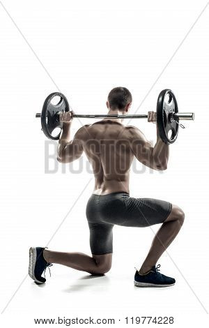 Fitness man standing on knee and holding barbell, rear view