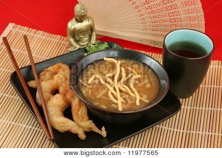 A delicious Chinese dinner of hot & sour soup, fried shrimp and tea.