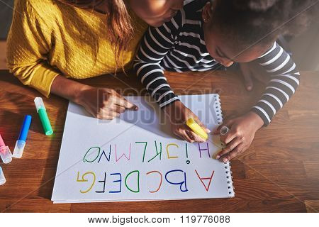 Overhead View Of Little Girl Learning The Alphabet