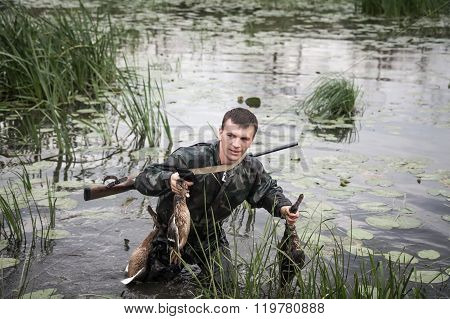 hunter man with prey after a successful hunt break through marshland