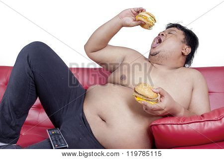 Obese Man Enjoy Two Hamburger On The Couch