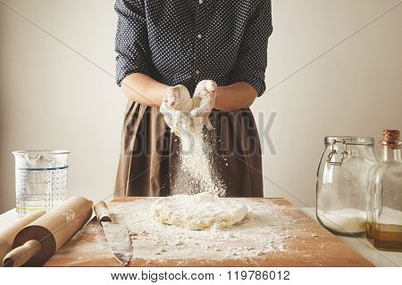 Woman Adds Some Flour To Dough On Wooden Table