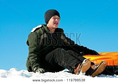 Teen Sitting In Snow With Tube