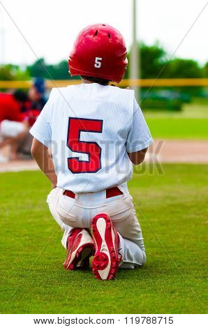 Young baseball boy sitting on field.