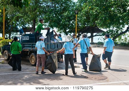 KRABI THAILAND - 13 OCT 2014: People outdoors collecting garbage along the street and waste off the beach in Ao Nang Krabi