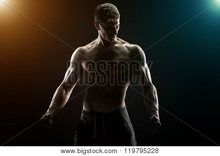 Sexy muscular man posing with naked torso in studio and looking behind on black background poster